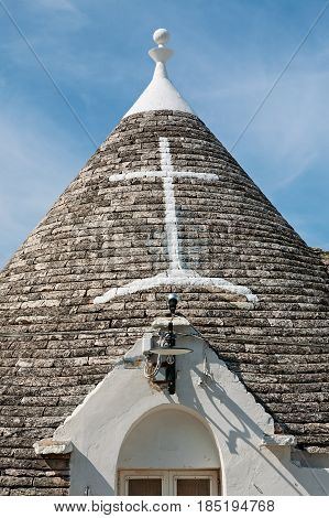Symbol in the Trullo conical rooftop in Alberobello under a blue sky Apulia Italy