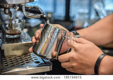 Barista steaming milk for hot cappuccino with machine