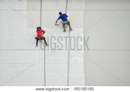Un safety Painters and harnesses hanging high building in construction sitehand brush color work concept