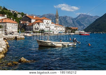 The historic old town of Perast sandwiched between the turquoise coloured water of The Bay of Kotor & the rugged mountains of the Montenegro coastline.