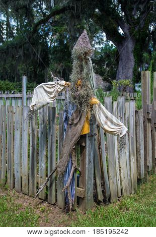 A real scarecrow by the fence in a garden.