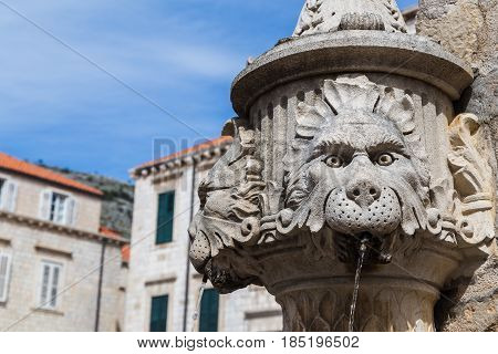 Water flowing out of the one of the faces on the Amerling fountain in Gundulic Square Dubrovnik.