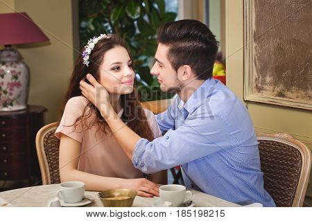 Young beautiful enamored couple sitting at a table in a cafe and drinking from cups