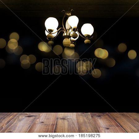 wooden floor tile and vintage chandelier light hanging under ceiling over bokeh background.