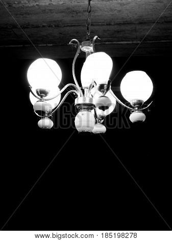 Vintage and rusty chandelier light hanging under ceiling