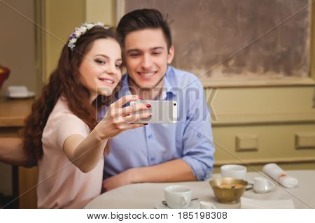 Young beautiful enamored couple sitting at a table in a cafeand making selfie