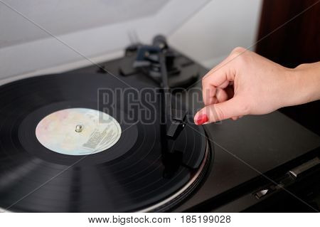 Woman listening to music using vintage vinyl record