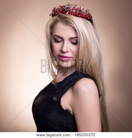 Close Up Portrait Of Young Beautiful Blond Woman In Crown Over Beige