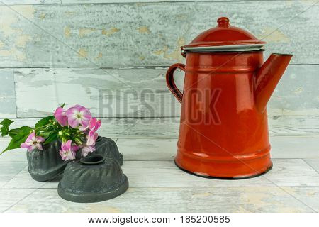 Red coffeepot with a colorful flower on a rustic white wooden background