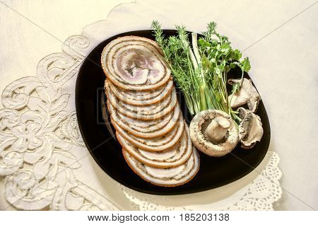 Black dish with herbs near with slices of meatloaf of tenderloin smoked pork