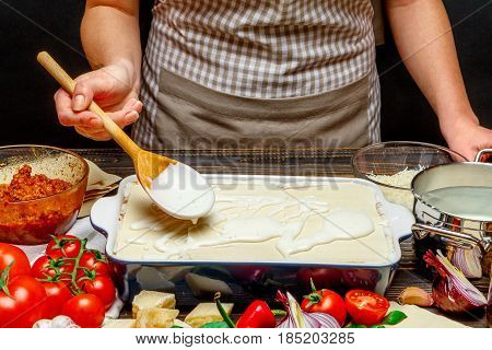 Preparation of homemade lasagna. Italian pasta recipe with tomato sauce and minced meat.