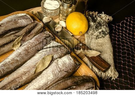 Rewarmed vitrified fish hake with bay leaf on tray from kitchen knifeolive oil with spices