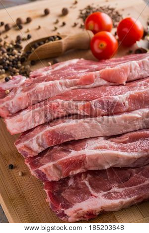 Several Slices Of Neck Pork Steak With Spice And Tomatoes