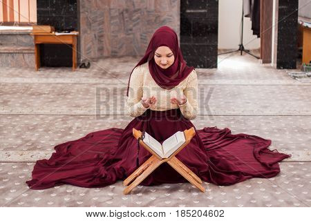 Young And Beautiful Girl Sitting Covered In Sumptuous Dress And Teaches The Qur'an, Which Is Located