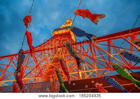 Tokyo, Japan - April 23, 2017: bottom view of Koinobori at Tokyo Tower by night. Koinobori are carp-shaped wind socks traditionally flown in Japan to celebrate Children's Day during the Golden Week.