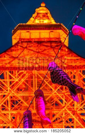 Tokyo, Japan - April 23, 2017: closeup of pink Koinobori a carp-shaped wind socks traditionally flown in Japan to celebrate Children's Day. Blurred Tokyo Tower by night on background. Vertical shot.