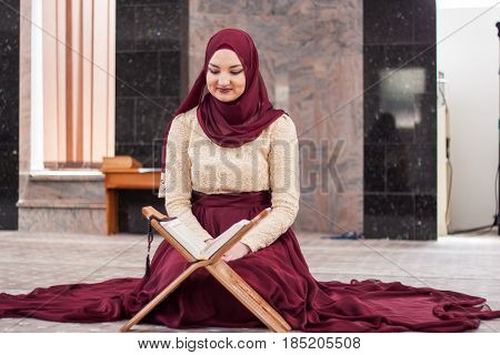 Young And Beautiful Girl Sitting Covered In Sumptuous Dress And Teaches The Quran, Which Is Located