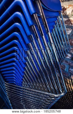 A lot of blue chairs are stacked high