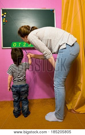 baby boy and the teacher stands at the blackboard in the classroom caused the teacher to the Board and a pointer shows the numbers 0 1 2 3 4