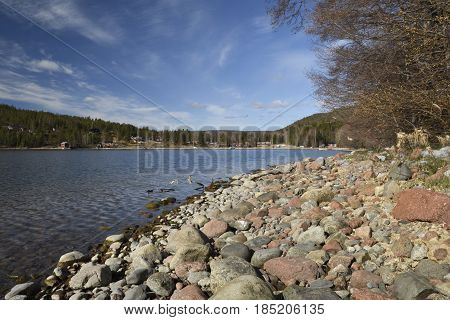 Bay with soft rounded granite stones at the sea shore picture from the North of Sweden.