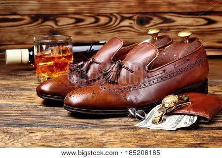 Brown brogues. Men's accessroiesgolden watchleather potmone wallet with money .Bottle and glas of whiskey defocused .Copy space poster