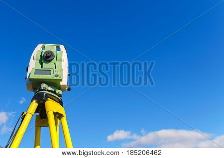 Modern surveyor equipment theodolite or tacheometer used in surveying and building construction for precise measurement. Total station outdoor against blue sky. Copy space.
