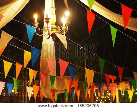 Night party decoration background vintage lamp and colorful flags.