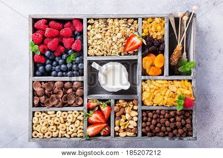 Variety of cold quick breakfast cereals with berries in old gray wooden box and other ingredients for breakfast, healthy eating concept, top view.