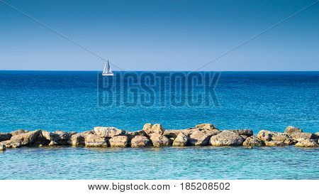 Blue sea with stones and white sailing vessel at background Cyprus