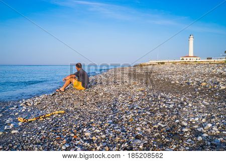 Lonely man on the beach with blue sky and lighthouse background