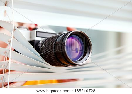 Person with Old Photo Camera spying through a Jalousie