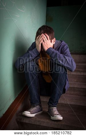 Sad Teenager sit on the Stairs in the Old Building