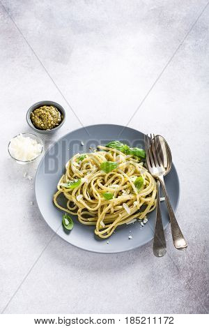 Homemade linguine pasta with green pesto and basil. Italian healthy food concept with copy space.