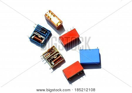 Electronic relay and capacitors on a white background