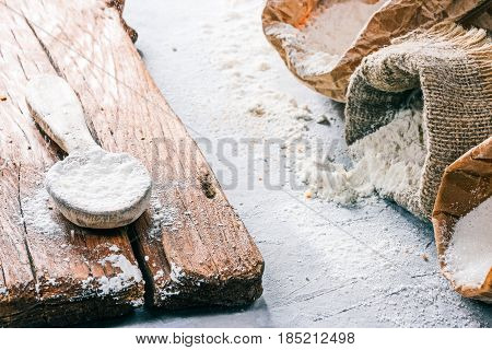 Packs of flour and sugar and rustic wood spoon of flour on the concrete background. Close up