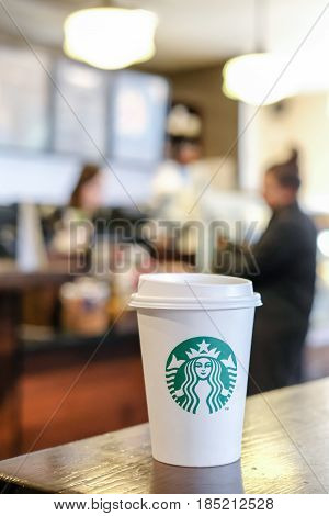 Edinburgh United Kingdom - 14 Febuary 2017 : Starbucks take away hot beverage coffee cup with logo on the table in store. Starbucks is one of the most world famous coffeehouse chain from USA