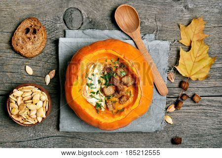 Dinner with pumpkin cream soup on wooden background healthy vegetarian food. Top view