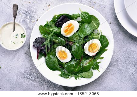 Healthy green salad with leaves and egg top view