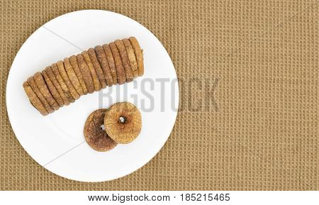 A plate of dried figs on a jute mat background