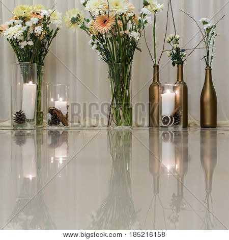 flowers. flowers bunches in glass vases and wine bottles and candles candlelight on glossy table surface indoors on white background. Celebration anniversary wedding decor