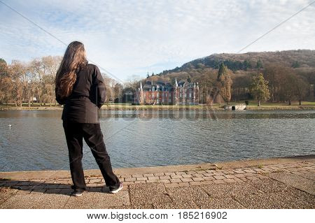 Namur Belgium - 2016 December 9 : The Dave castle near Namur on the river banks of the Meuse with a woman admiring the landmark Belgium