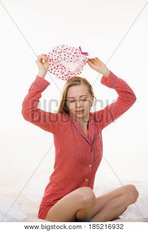 Young Woman Wearing Pink Pajamas Putting Bathing Cap