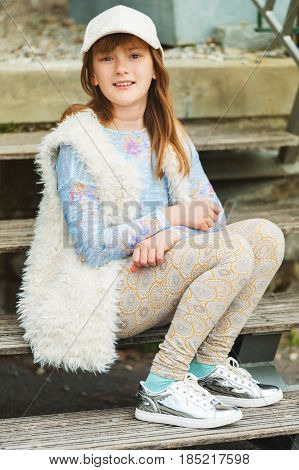 Outdoor fashion portrait of young preteen kid girl wearing white cap, faux fur gilet and silver mirror trainers