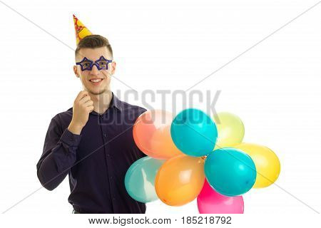 perky young guy keeps near eye paper glasses and lots of colored balls is isolated on a white background