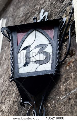 Street Lantern With House Number Hanging Outside The Building On The Street. Number Thirteen, 13