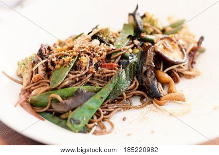 Buckwheat noodles with vegetables and mushrooms on plate, close-up, toned image