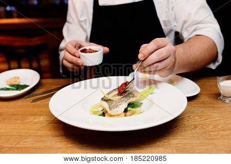 Chef is adding tomato sauce to a fish dish, toned image
