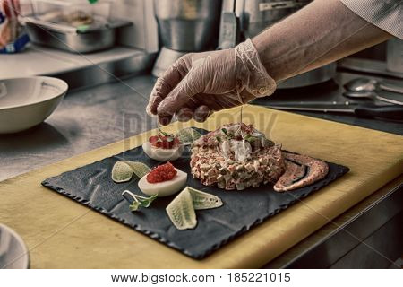 Chef is decorating crab salad in restaurant kitchen, toned image