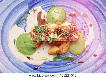 Chicken fillet on blue porcelain plate, unusual food design, toned image
