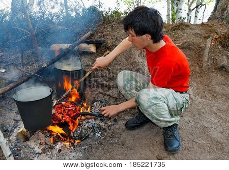A teenager cooks food on an open fire in an expedition